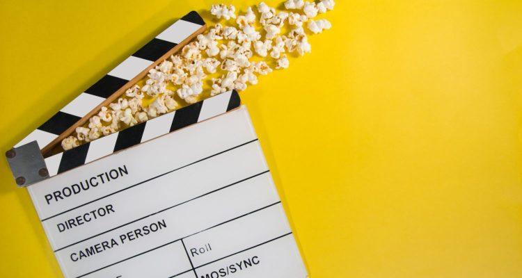 Filmklappe und Popcorn auf gelbem Grund