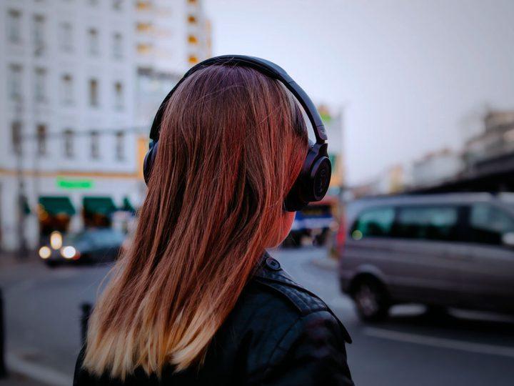 Hinterkopf einer Frau mit Teufel Kopfhörer.