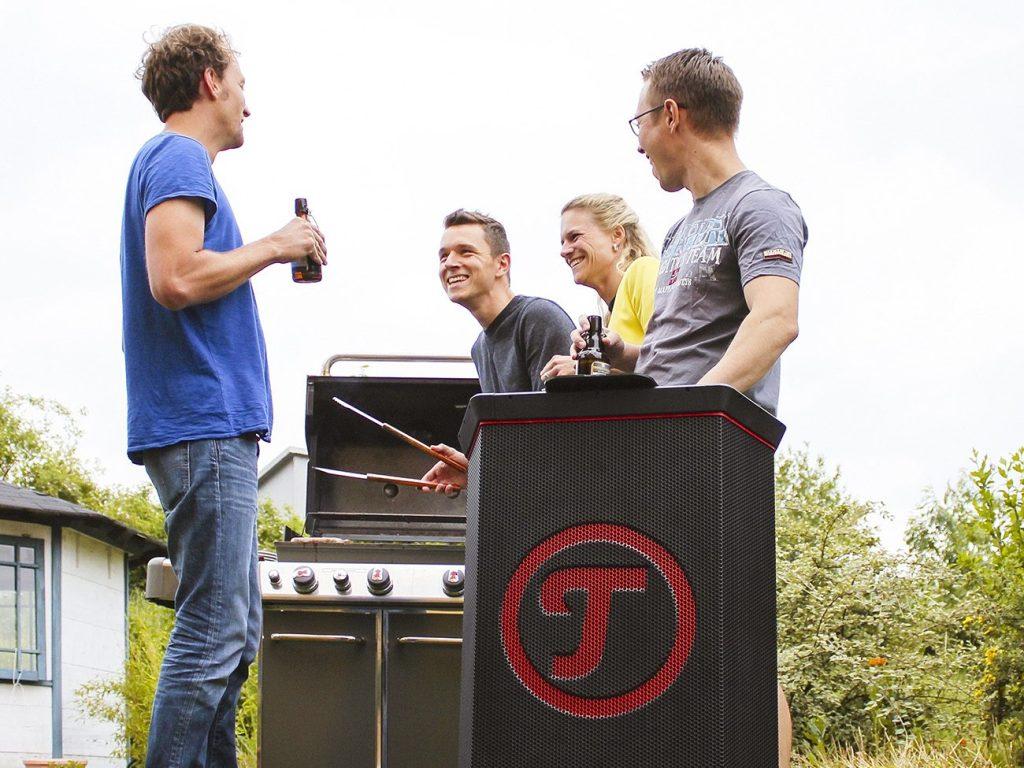 Fröhliche Freunde am Grill, im Vordergrund ROCKSTER Lautsprecher