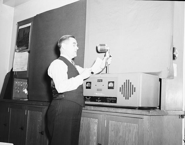 Man vor einem alten Radioapparat