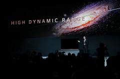 Ein Mann im Anzug zeigt auf einen Dolby Vision HDR-Fernseher