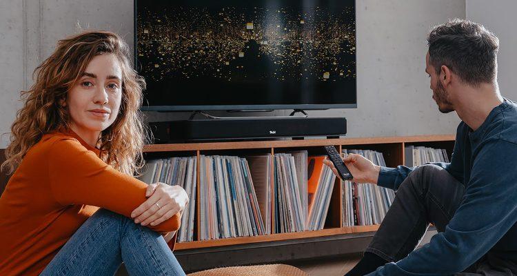 Frau und Mann im Wohnzimmer vor Sounddeck und TV