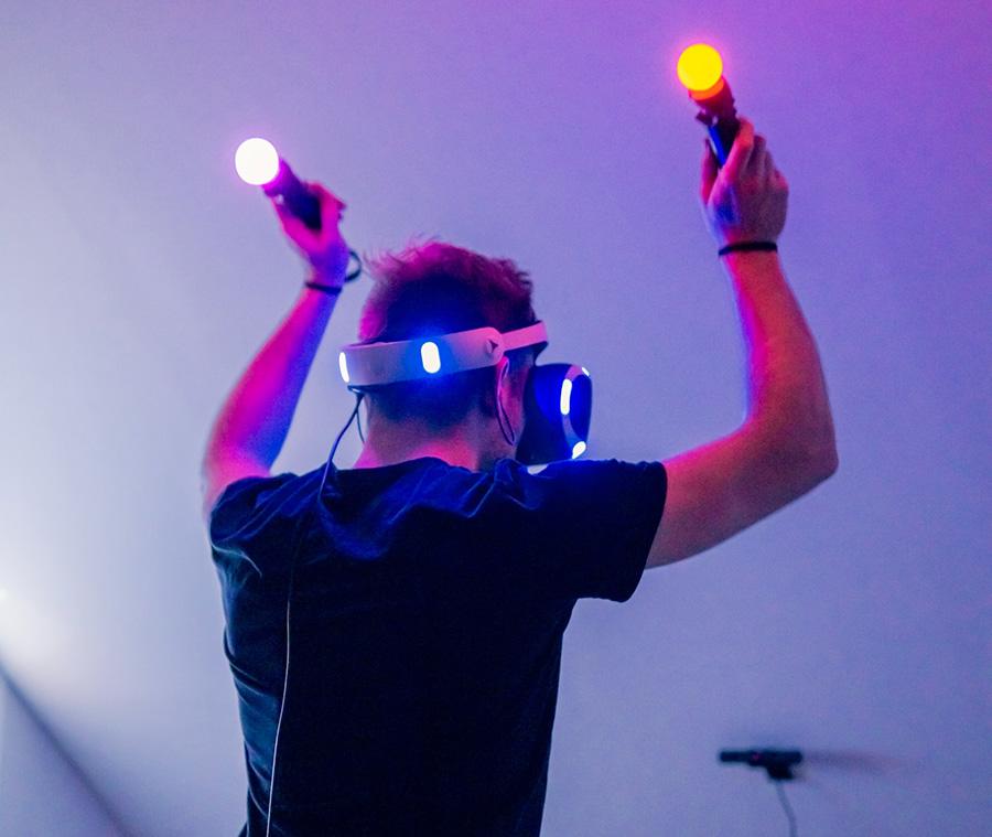 Mann mit PlayStation VR-Brille und Move Controllern