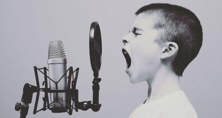 Junge steht vor einem Studio-Mikrofon und ruft etwas hinein