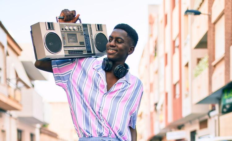 Junger Mann mit Ghettoblaster und Kopfhörer