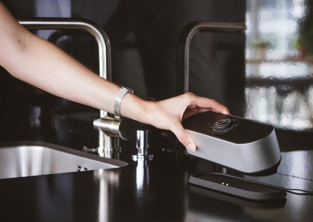 Arm der einen tragbaren Lautsprecher auf einer Küchenarbeitsfläche abstellt.