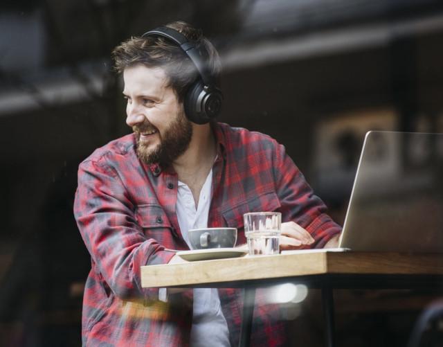 Man mit Bluetooth-Kopfhörern in einem Cafe