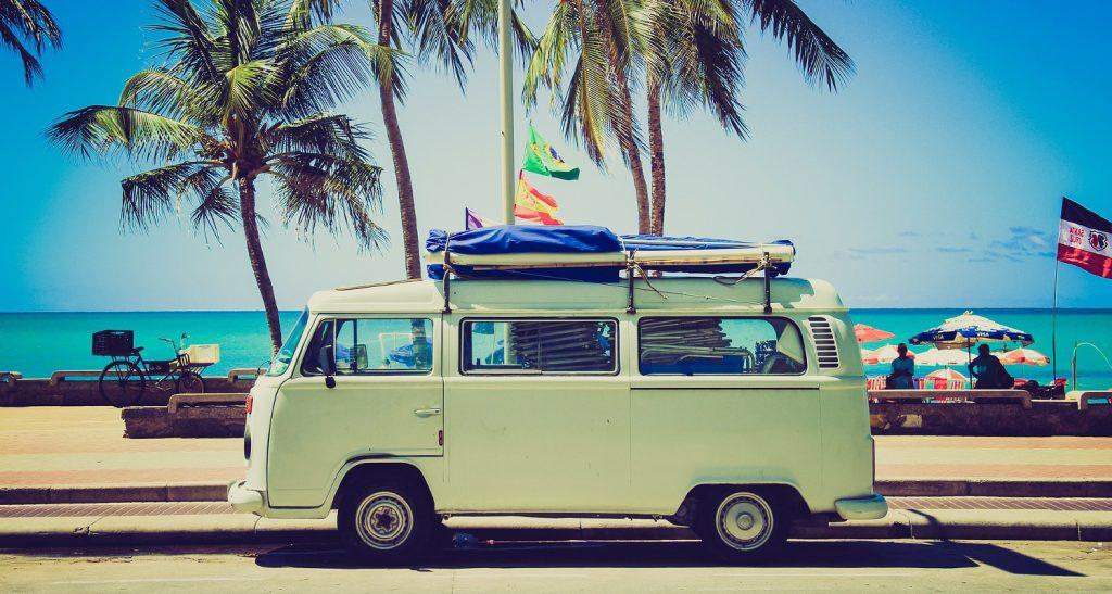 Alter VW-Bulli vor einem Horizont mit Meer und Palmen.
