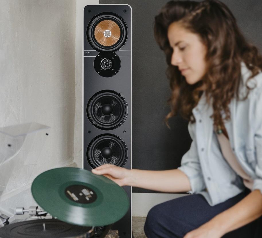 Frau legt Vinyl in Plattenspieler, im Hintergrund Lautsprecher