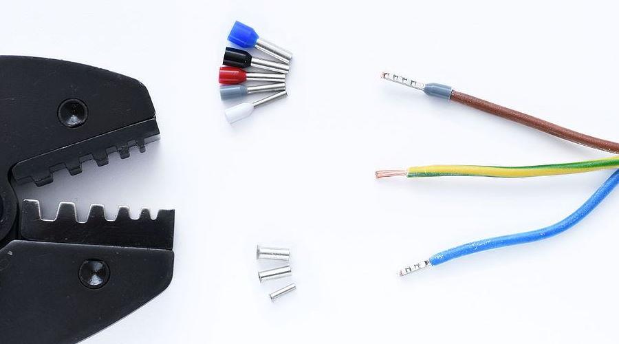 Abisolierte Kabel, verschiedene Aderendhülsen und Zange
