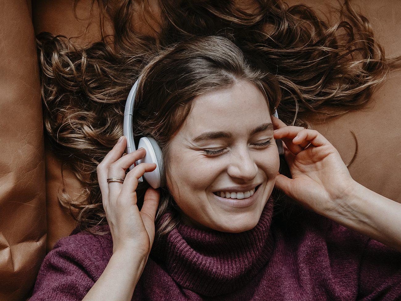 Fröhliche Frau mit Airy Kopfhörer