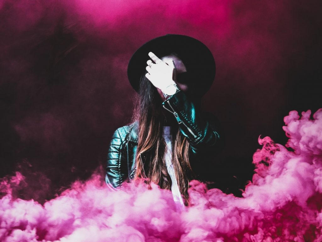 Indie-rock fan surrounded by pink smoke