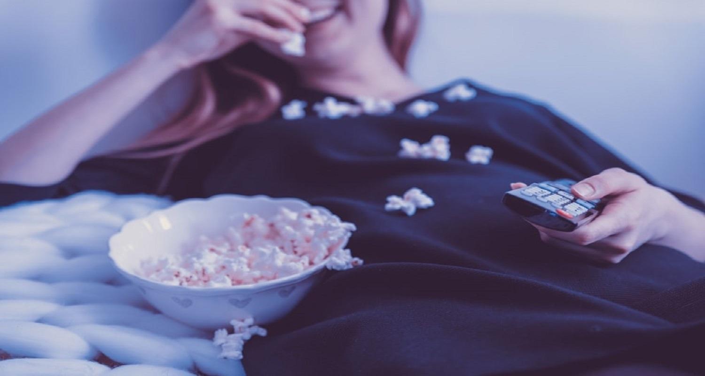 Frau mit Fernbedienung in der Hand sitzt auf Sofa und isst Popcorn