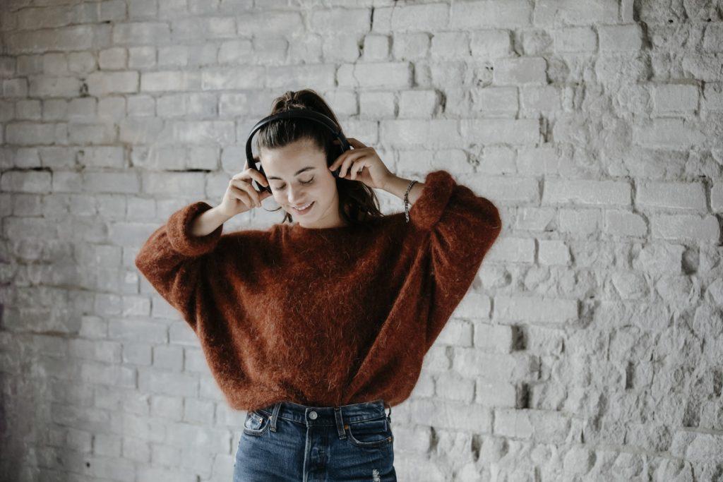 Frau hört Musik über Teufel Kopfhörer.