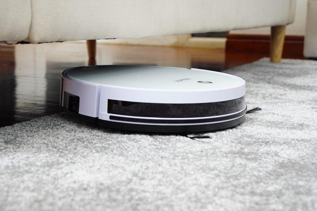 Staubsaugerroboter reinigt den Wohnzimmerteppich.