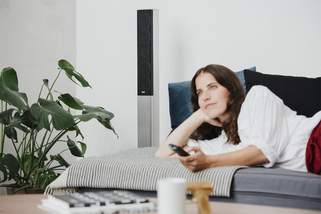 Frau schaut Fernsehen mit Lautsprechern im Hintergrund