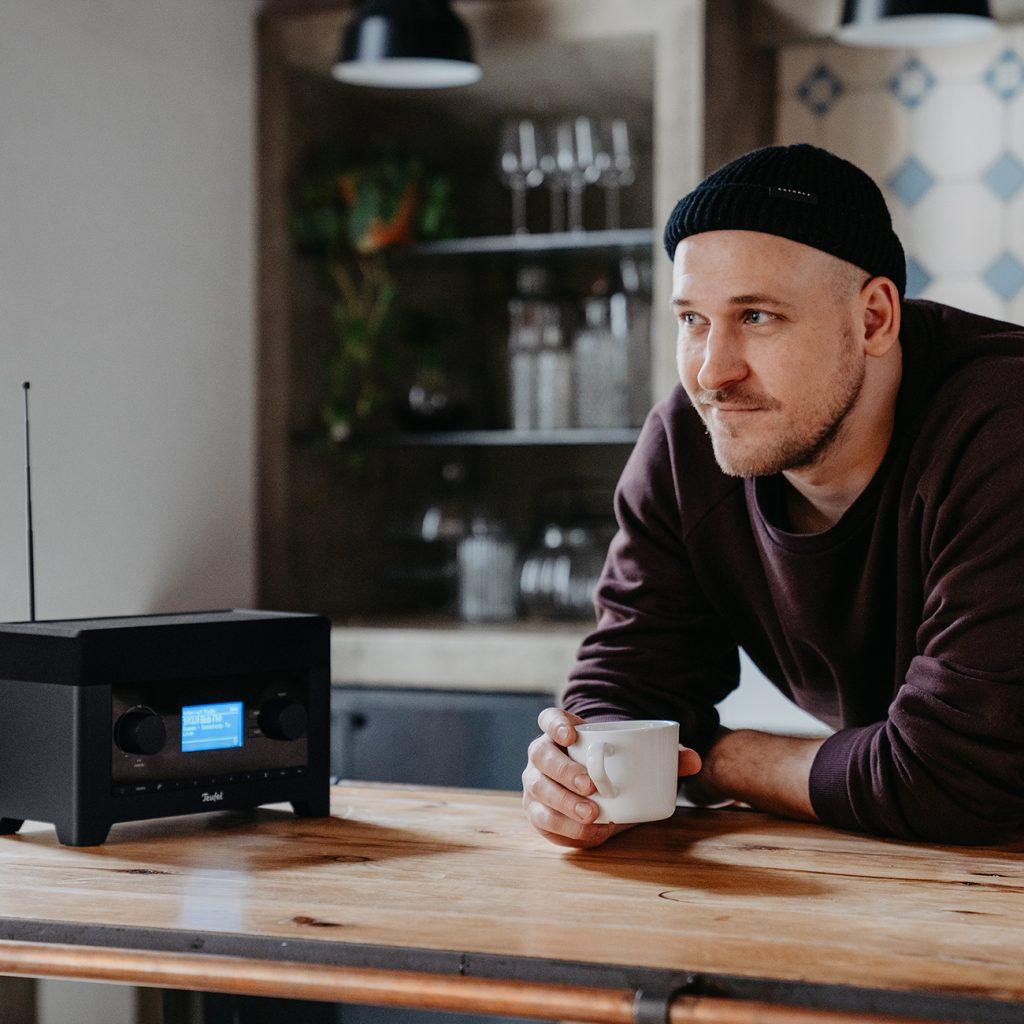 Mann trinkt Kaffee und hört Radio.