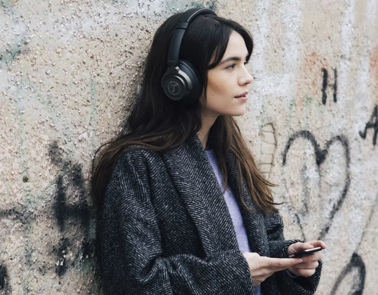 Frau hört unterwegs Podcasts mit Kopfhöer REAL BLUE NC.