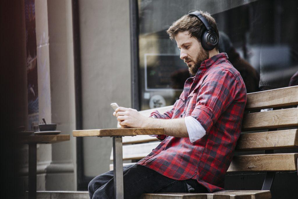 Mann vor Café mit Kopfhörern