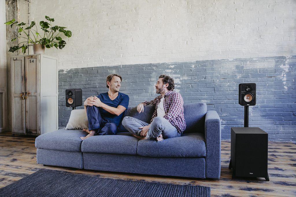 Zwei Freunde unterhalten sich im Wohnzimmer.