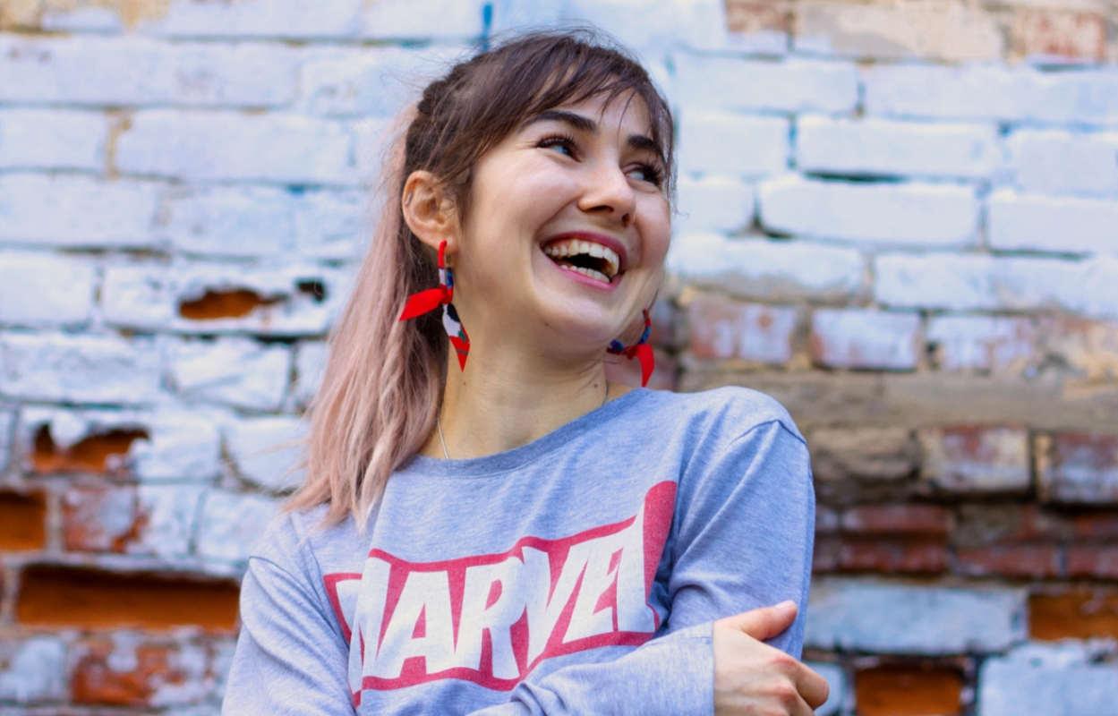 Lachende junge Frau im Marvel-Pullover.