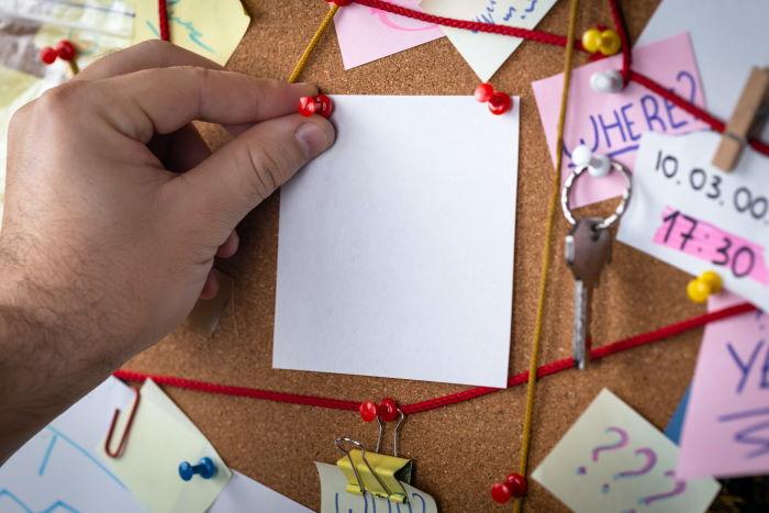 Pinnwand mit Hinweise, Zetteln und Bändern