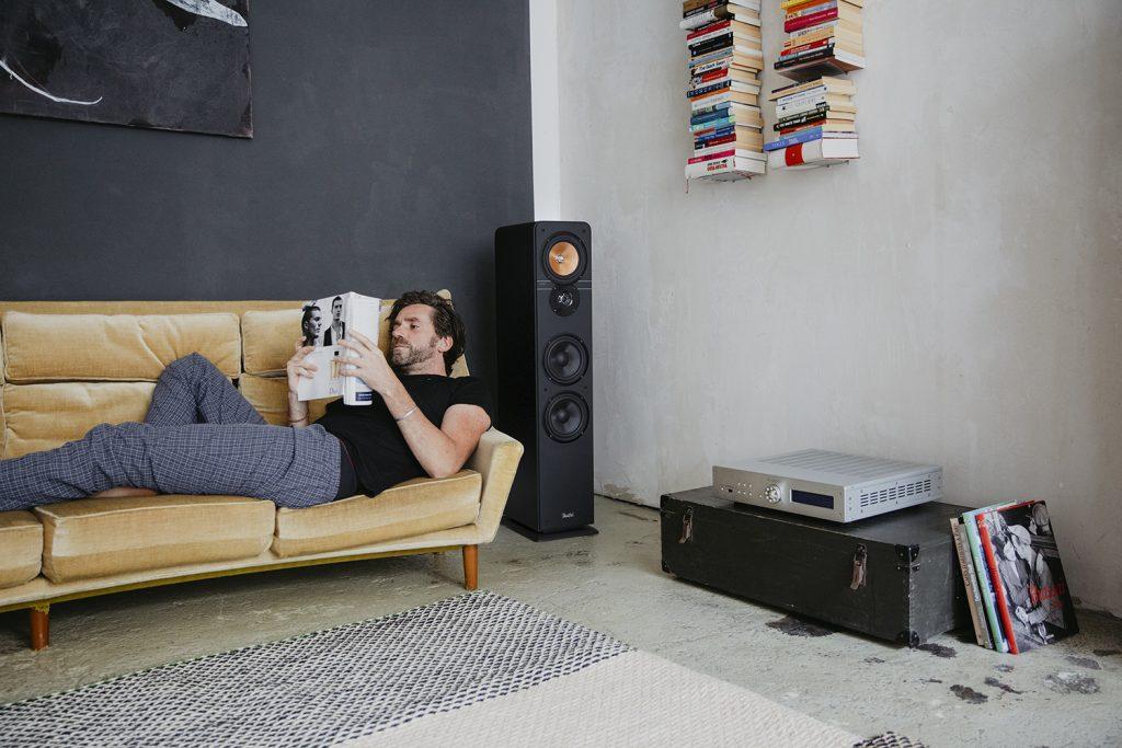Mann liest Zeitschrift und hört Musik über die HiFi-Anlage.