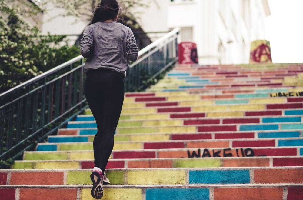 Frau joggt Treppen hoch.