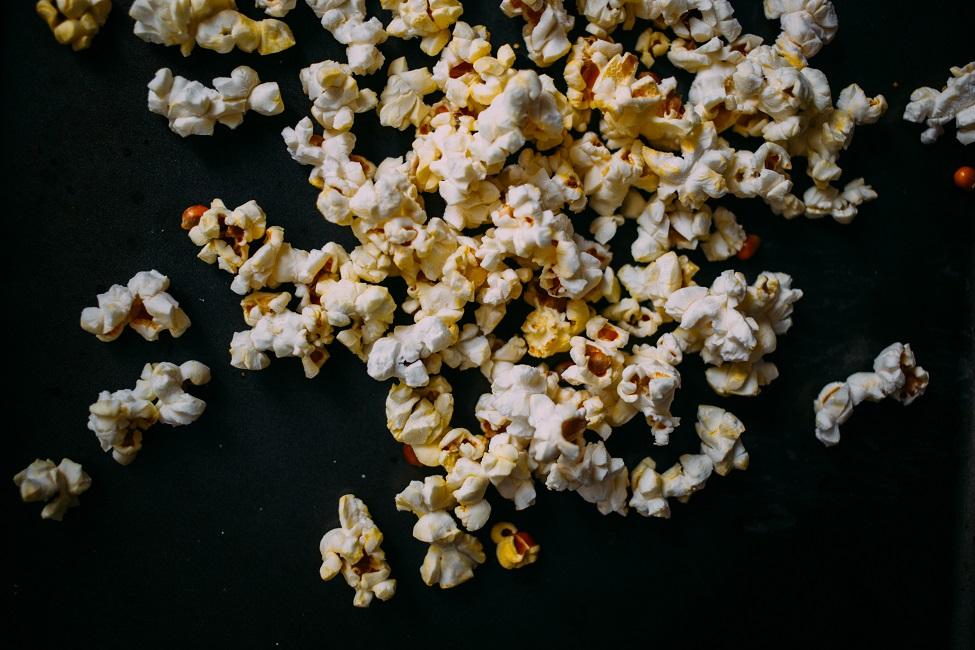 Verstreutes Popcorn auf schwarzem Untergrund.