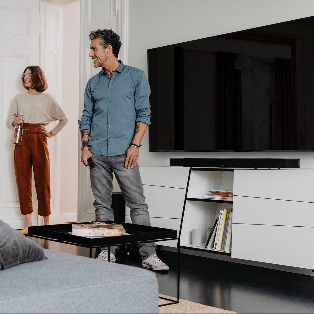 Freunde im technisch voll ausgestattetem Wohnzimmer.