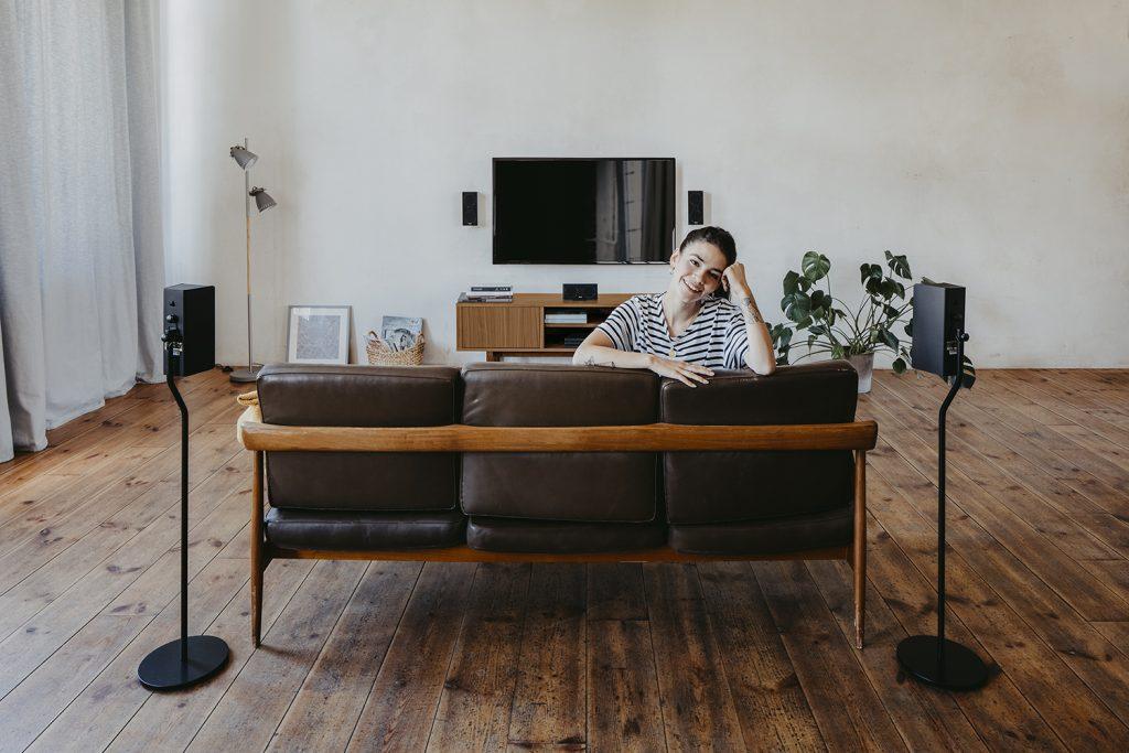 Frau im Wohnzimmer vor Heimkinoanlage.