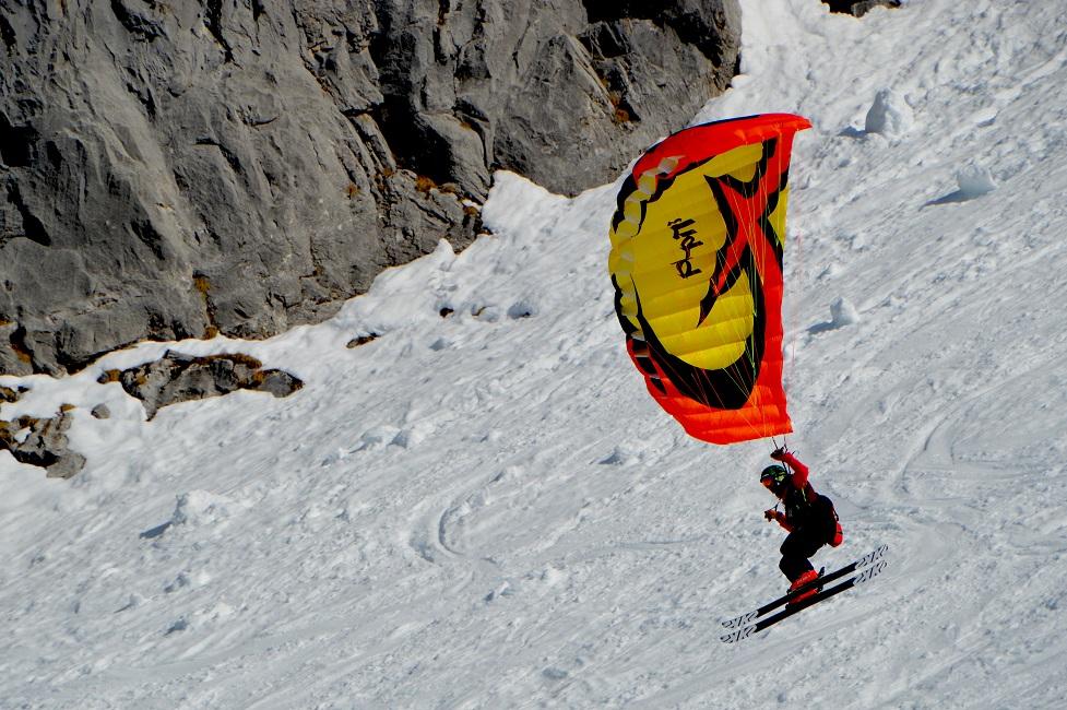 Person mit Skiern und Gleitschirm.