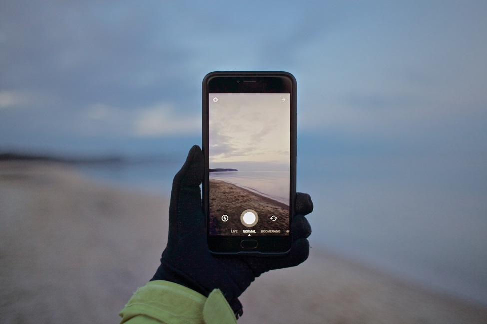 Person macht Urlaubsfoto mit seinem Smartphone.
