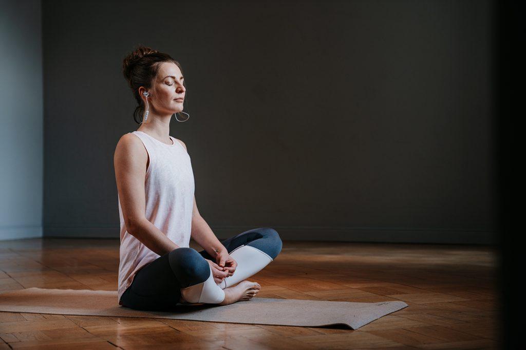 Frau entspannt mit Yoga und Musik.