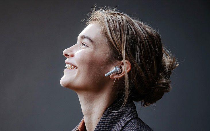 Lachende Frau mit AIRY TRUE WIRELESS Kopfhörern