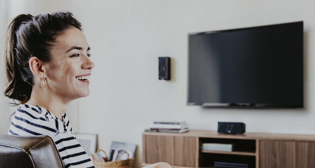 Lachende Frau vor Fernseher und kleinem Lautsprecher