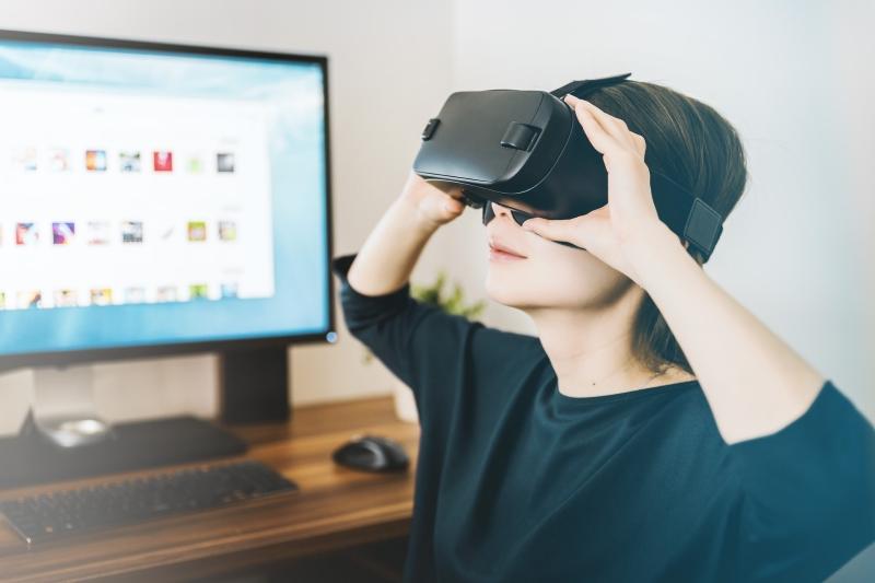 Frau vor Laptop mit VR-Brille