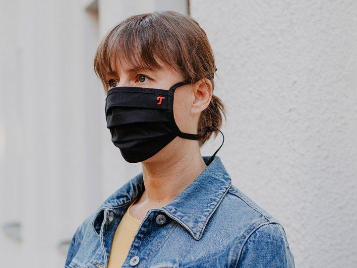 Frau trägt Teufel Maske vor Häuserwand