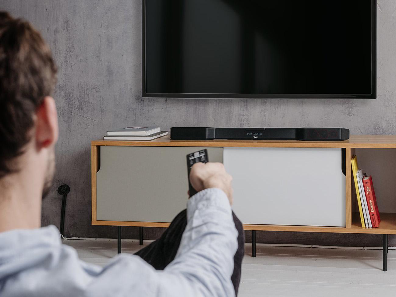 Mann auf Sofa vor Fernseher und Cinebar