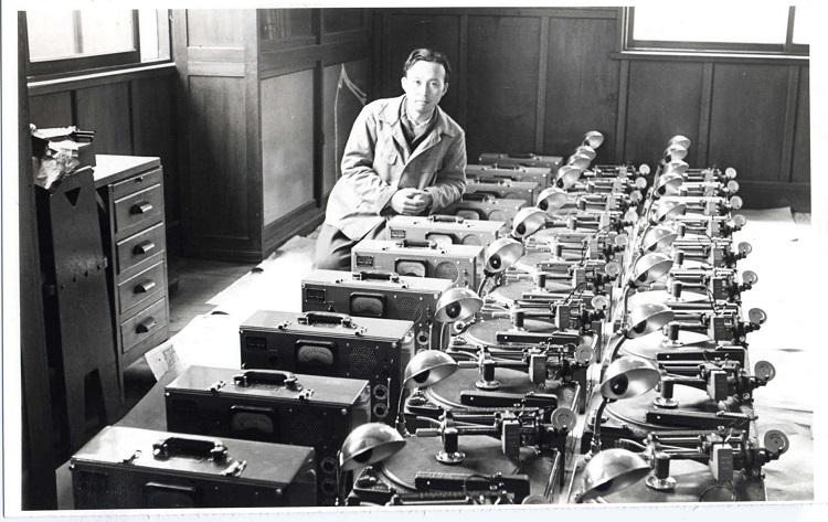Schwarz-weiß Fotografie Mitarbeiter Denon neben aufgereihten Geräten