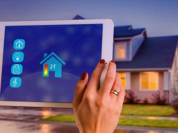 Haus im Hintergrund Hände mit Tablet im Vordergrund