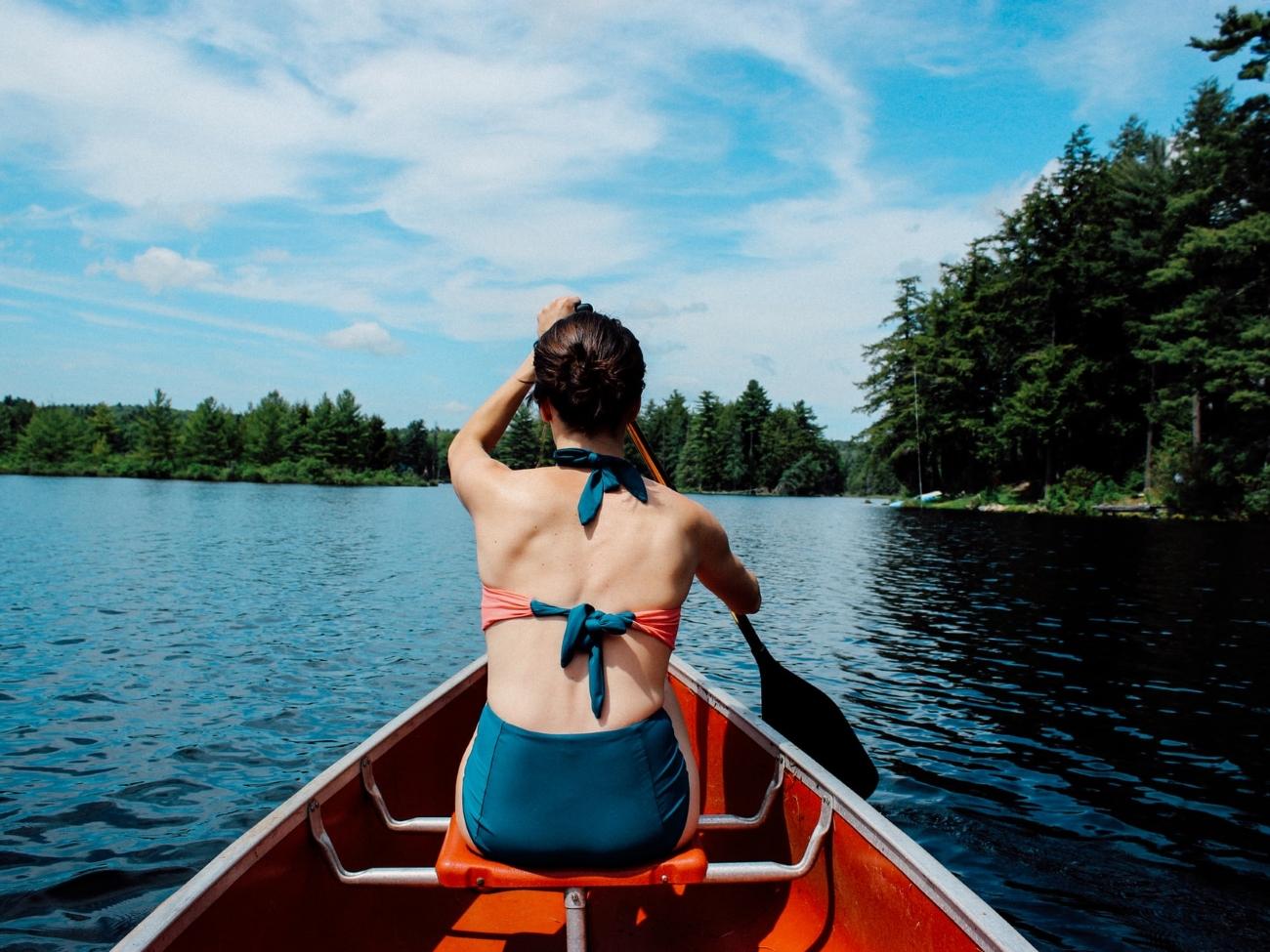 Junge im Boot sitzende Frau von hinten, die auf einem See paddelt.