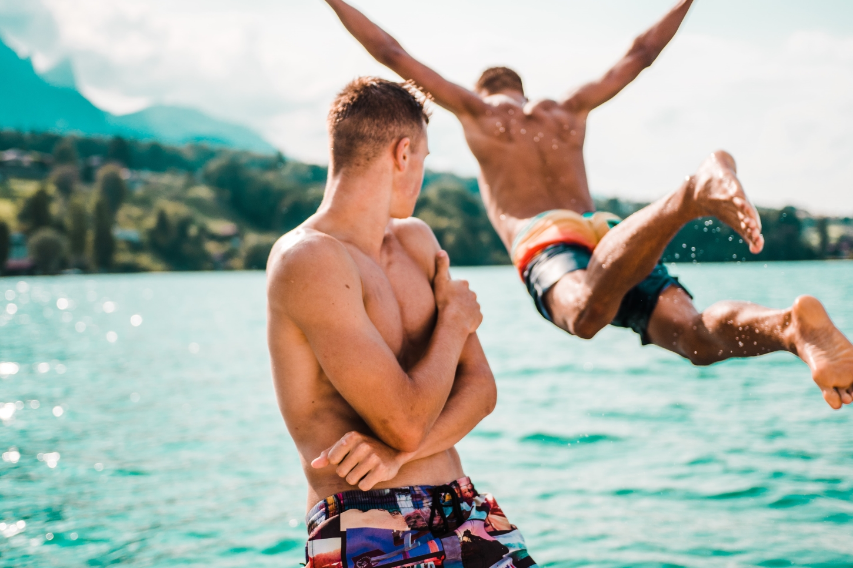 Zwei junge Männer am Seeufer, von denen einer ins Wasser springt.