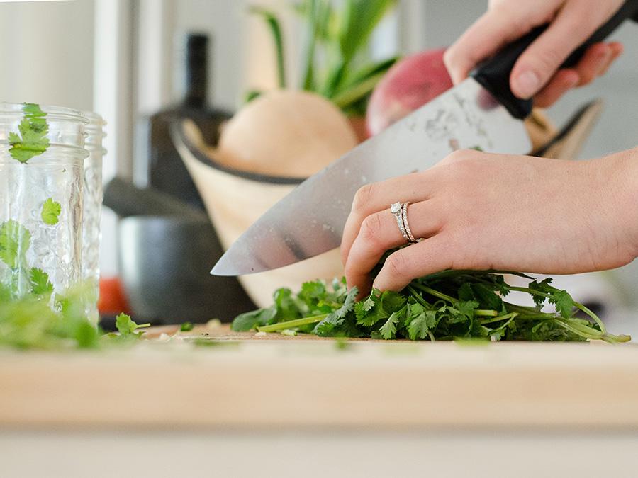 Hände die Kräuter schneiden in Küche