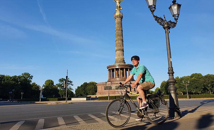 Moderator Alex Schurig auf dem Fahrrad vor der Siegessäule in Berlin