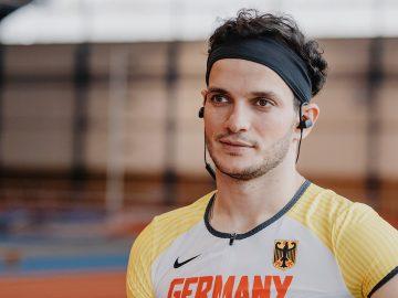 Junger Mann in Sportkleidung mit In-Ear-Kopfhörern.