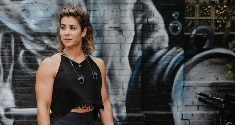 Junge Frau in Sportkleidung steht vor einer mit Graffitis besprühten Steinwand.