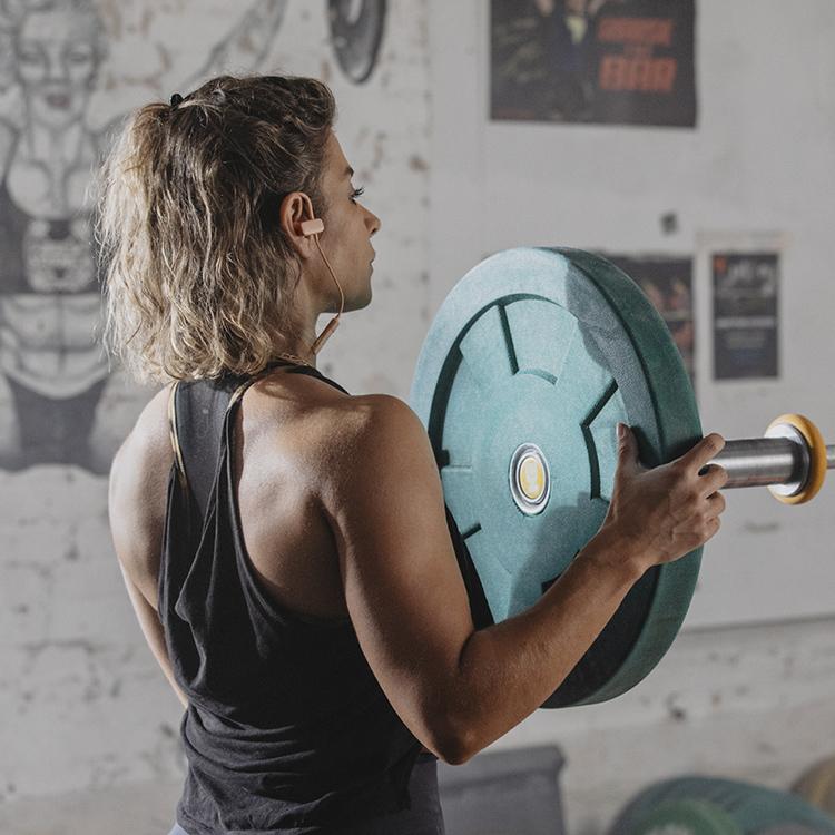 Junge Frau bringt Gewicht an einer Langhantel an.