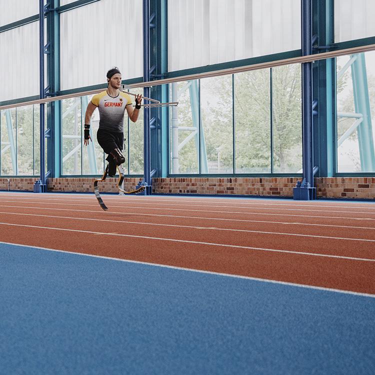 Junger Mann läuft in einer Sporthalle auf Beinprothesen.