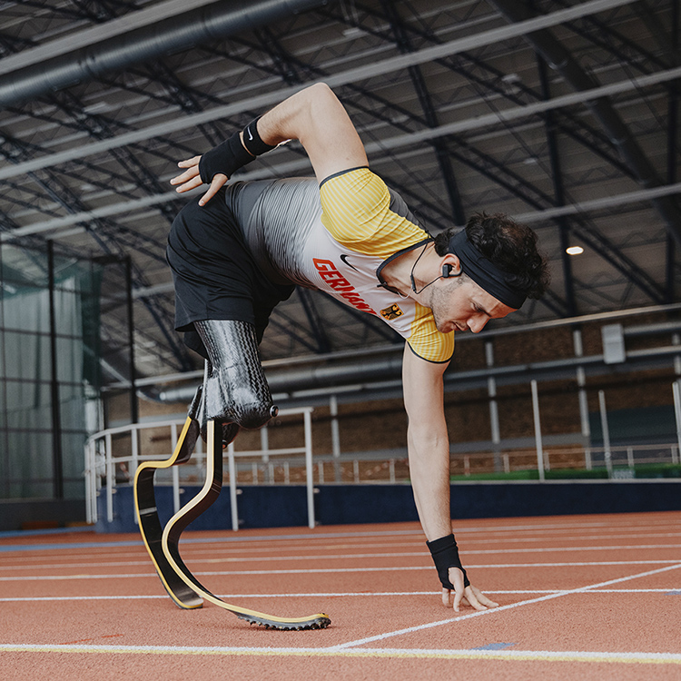 Junger Mann mit Beinprothesen in der Sprint-Startposition in einer Sporthalle.